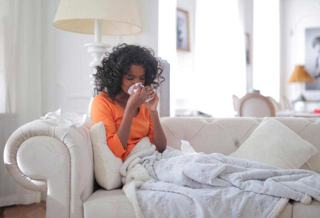 Woman sitting on couch, sneezing